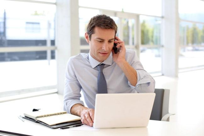 Man i skjorta sitter på kontoret och pratar i telefon framför datorn