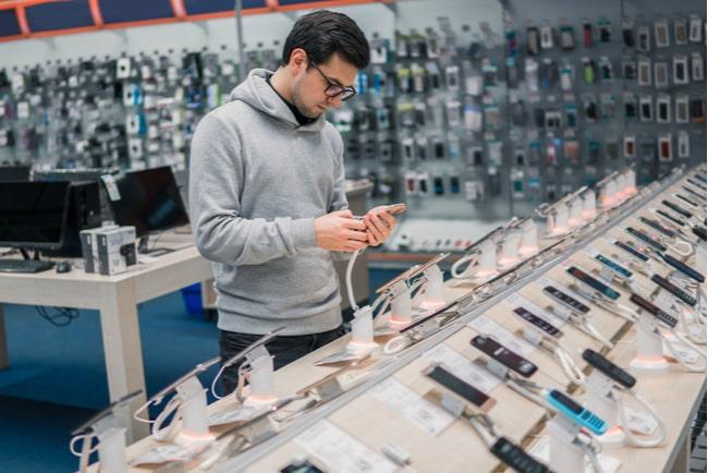 Man tittar på telefoner i elektronikaffär