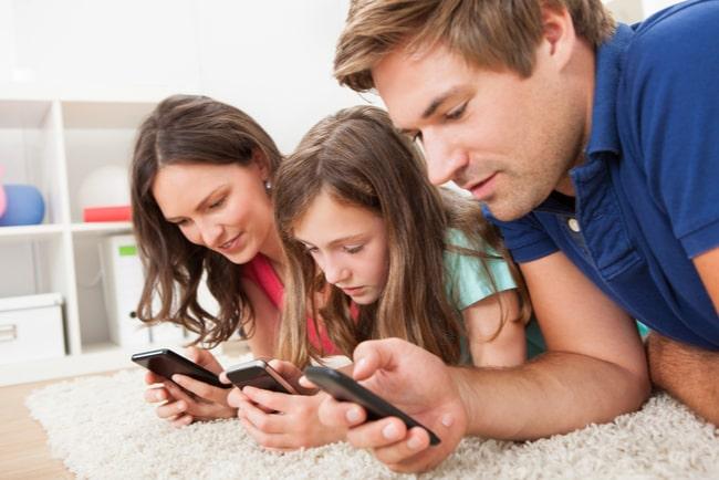 Familj surfar på varsin telefon