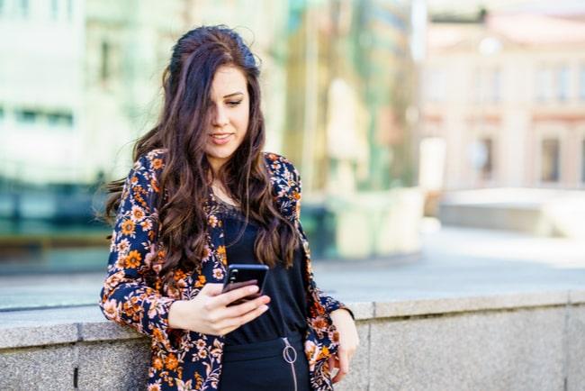 Kvinna står och surfar på mobiltelefon