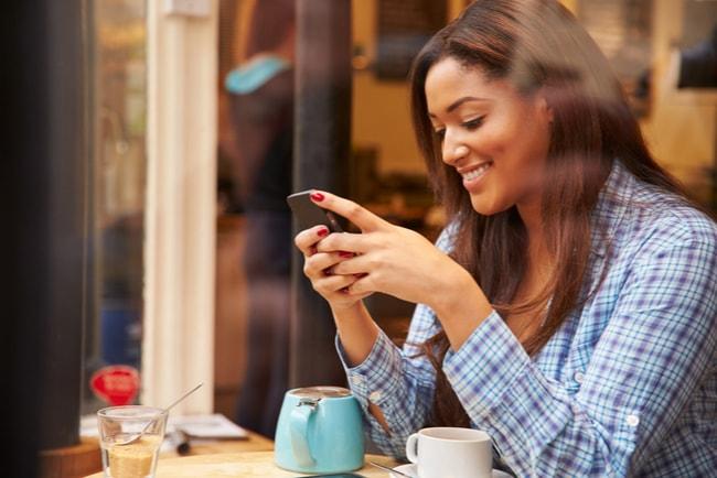 leende kvinna på café med smartphone i handen