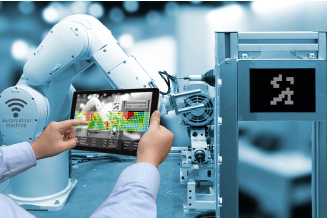 man håller skärm framför en trådlös robot i smart industrimiljö