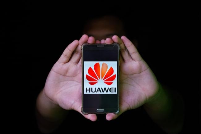händer håller fram huaweitelefon mot svart bakgrund