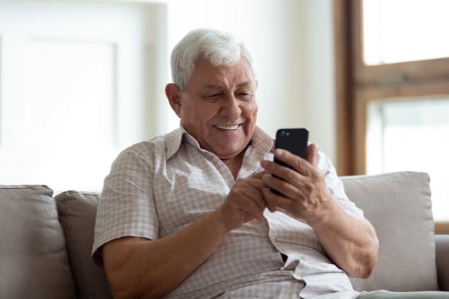 äldre man tittar på mobil