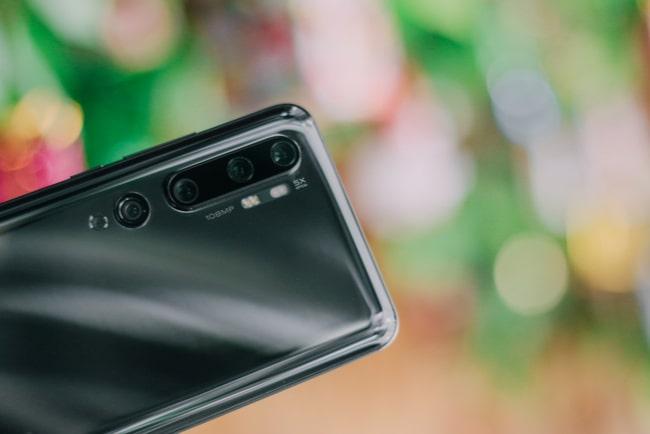 svart mobil i förgrunden mot suddig bakgrund