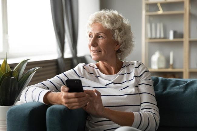 äldre kvinna med mobil tittar ut genom fönstret