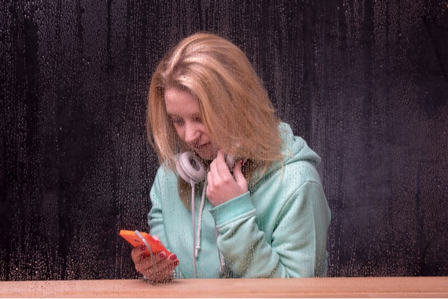 kvinna med telefon innanför regntäckt fönster