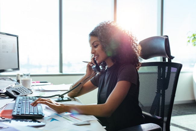 kvinnlig entreprenör pratar i telefon och arbetar på dator vid skrivbord