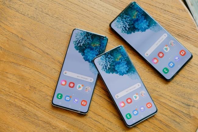 tre telefoner ur Samsungs S20-serie på träbord