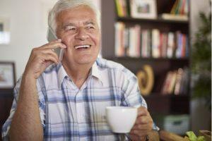 äldre man pratar i telefon i vardagsrum med en kaffekopp i handen