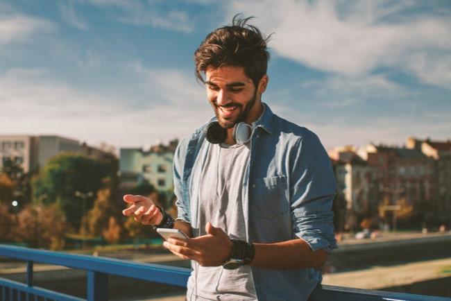 glad man med smartphone med stadsmiljö i bakgrunden