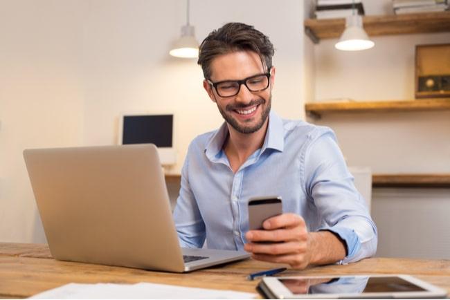 glad man med dator och telefon vid skrivbord