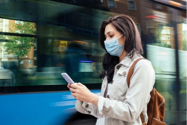 kvinna med munskydd använder mobiltelefon medan buss kör förbi i bakgrunden
