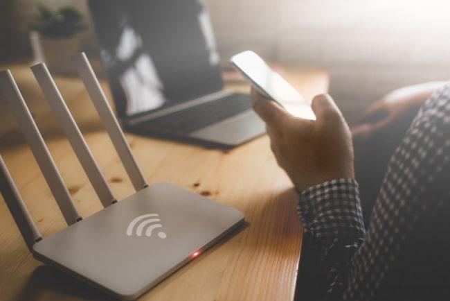 närbild på trådlös router och en person med smartphone och laptop vid köksbord