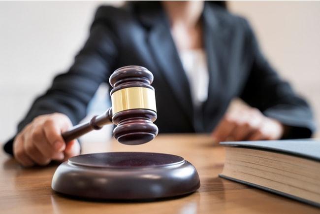 domare med domarklubba i rättssal