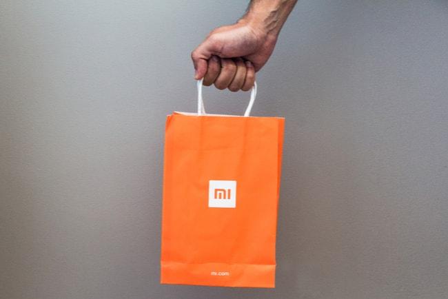 hand håller fram shoppingpåse med xiaomis logga