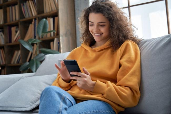 glad ung kvinna med mobiltelefon i soffa