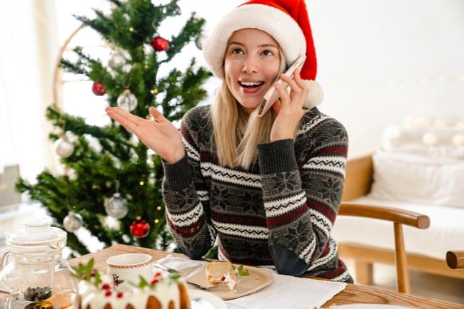 ung kvinna i tomteluva pratar i mobiltelefon vid bord med juldekorationer