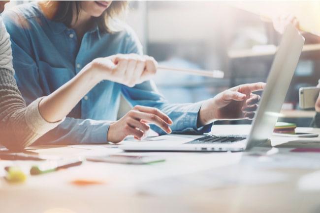 två medarbetare framför laptop vid skrivbord