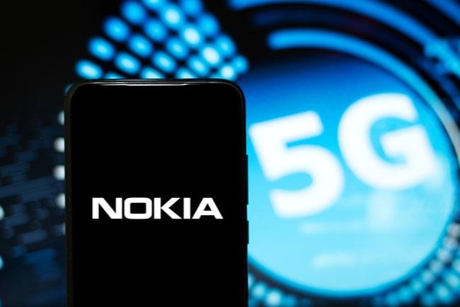 nokias logotyp på smartphone med 5G-symbol i bakgrunden