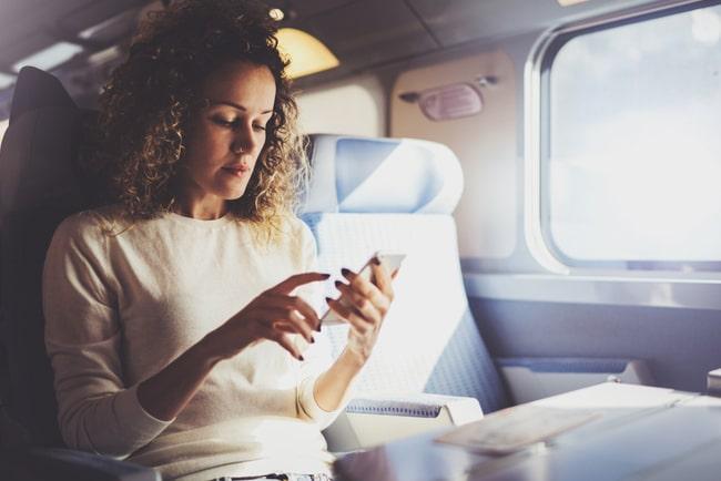 kvinna med mobiltelefon på tåg