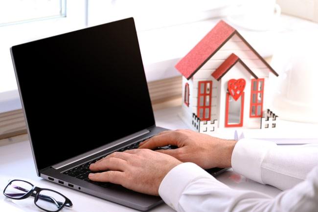 man knappar på dator med modellhus bredvid