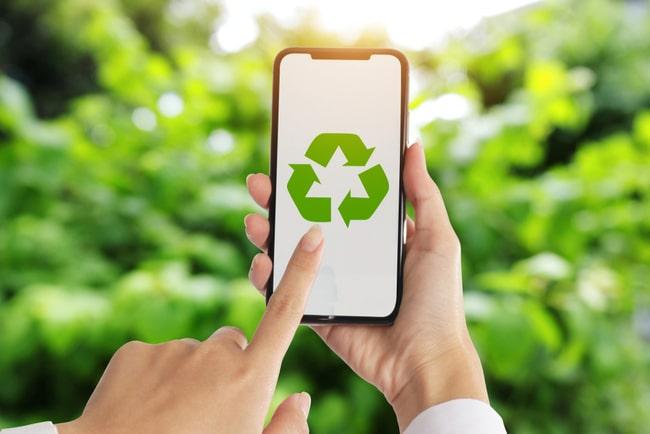kvinna håller mobil med återvinningssymbol