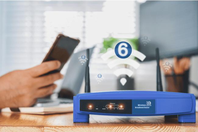 wifi 6 router med person med smartphone och dator i bakgrunden