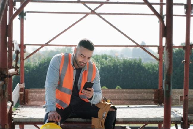 Byggarbetare sitter ned och surfar på sin telefon
